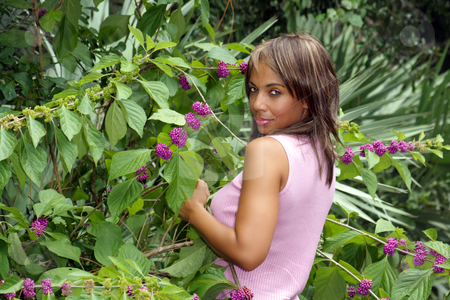 Beautiful Black Woman Outdoors (4) stock photo, A beautiful mature black woman soaks up some atmosphere amidst colorful, lush tropical vegetation outdoors, looking over her shoulder into the camera. by Carl Stewart
