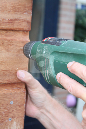 Working with a Power drill  stock photo, Working with a Power drill on a wooden construction by Porto Sabbia