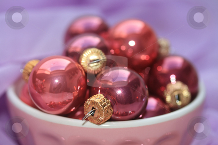 Pink and purple christmas decorations stock photo, A bowl with pink christmas balls on a purple background by Porto Sabbia