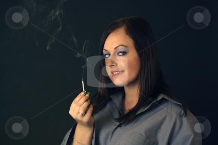 Beautiful Brunette Holds a Smoldering Match stock photo, A lovely young brunette holds a smoldering, smoking kitchen match. by Carl Stewart