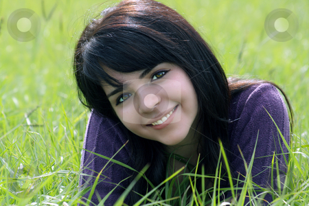 Beautiful Brunette in a Grassy Field (2) stock photo, Close-up of a lovely young brunette with a bright, warm smile lying in a field of tall green grass. by Carl Stewart