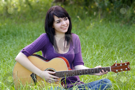 Beautiful Brunette Outdoors with a Guitar (1) stock photo, A lovely young brunette sits in a field of tall green grass with her acoustic guitar, looking off camera to frame right. by Carl Stewart