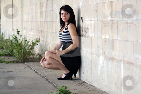 Beautiful Brunette at a Block Wall (1) stock photo, A lovely young brunette squats and leans against a block wall, looking at the camera with a serious facial expression. by Carl Stewart