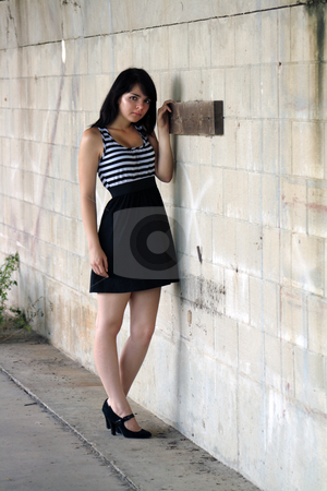 Beautiful Brunette at a Block Wall (3) stock photo, A lovely young brunette stands leaning against a block wall, looking at the camera with a serious facial expression. by Carl Stewart