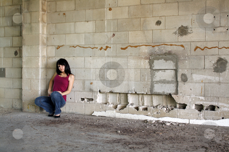 Beautiful Brunette at a Block Wall (5) stock photo, A lovely young brunette squats and leans against a block wall, looking at the camera with a serious facial expression.  Wide shot with the model in the lower left frame, leaving plenty of room for insertion of graphics, logos, etc. by Carl Stewart