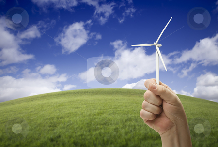 Male Fist Holding Wind Turbine Outside with Grass Field stock photo, Male Fist Holding Wind Turbine Outside with Grass Field, Sky and Clouds. by Andy Dean
