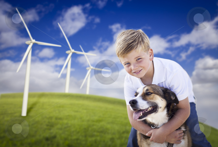 Young Boy and Dog in Wind Turbine Field stock photo, Handsome Young Blue Eyed Boy and Dog Playing Near Wind Turbines and Grass Field. by Andy Dean