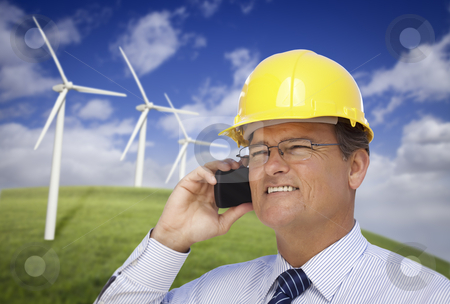 Hard Hat Wearing Engineer on Phone with Turbines Behind stock photo, Hard Hat Wearing Engineer on Cell Phone with Wind Turbines Behind Him. by Andy Dean