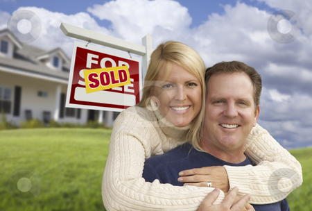 Happy Couple Hugging in Front of Sold Sign and House stock photo, Happy Couple Hugging in Front Yard with Sold Real Estate Sign and House. by Andy Dean
