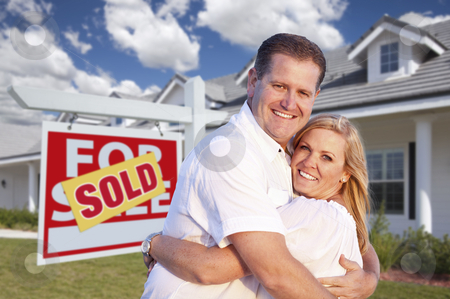 Couple Hugging in Front of Sold Sign and House stock photo, Happy Couple Hugging in Front of Sold Real Estate Sign and House. by Andy Dean