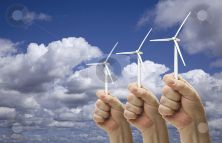 Male Fists Holding Three Wind Turbines Outside stock photo, Male Fists Holding Three Wind Turbines Outside with Clouds and Sky. by Andy Dean