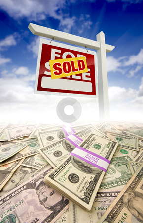Stacks of Money Fading Off and Sold For Sale Real Estate Sign Against Sky stock photo, Stacks of Money Fading Off and Sold For Sale Real Estate Sign Against Blue Sky with Clouds. by Andy Dean