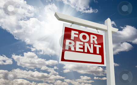 Left Facing For Rent Real Estate Sign Over Sunny Sky stock photo, Left Facing For Rent Real Estate Sign Over Clouds and Sunny Sky with Room for Text. by Andy Dean