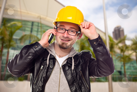 Young Cunstruction Worker on Cell Phone In Front of Building stock photo, Smiling Young Cunstruction Worker Talking on Cell Phone In Front of Building. by Andy Dean