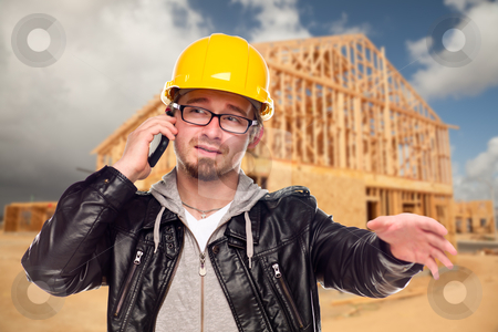 Young Cunstruction Worker on Cell Phone In Front of House stock photo, Young Contractor Wearing Hard Hat on Cell Phone In Front of Construction Site. by Andy Dean