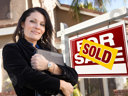 Female Hispanic Real Estate Agent, Sold For Sale Real Esate Sign stock photo, Proud, Attractive Hispanic Female Agent In Front of Sold For Sale Real Estate Sign and House. by Andy Dean