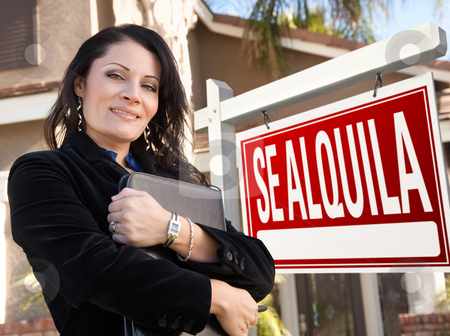 Female Hispanic Real Estate Agent, Se Alquila Sign and House stock photo, Proud, Attractive Hispanic Female Agent In Front of Spanish Se Alquila Real Estate Sign and House. by Andy Dean