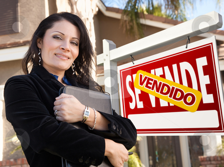 Female Hispanic Real Estate Agent, Vendido Se Vende Sign and Hou stock photo, Proud, Attractive Hispanic Female Agent In Front of Spanish Vendido Se Vende Real Estate Sign and House. by Andy Dean