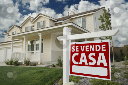 Se Vende Casa Spanish Real Estate Sign and House stock photo, Se Vende Casa Spanish Real Estate Sign and House and Blue Sky with Clouds. by Andy Dean