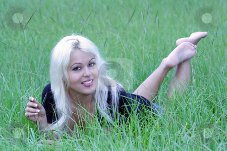 Sexy Blonde Lying in a Grassy Field (7) stock photo, A beautiful young platinum blonde with a bright, warm smile lying in a grassy field. by Carl Stewart