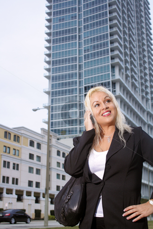 Beautiful Businesswoman Outdoors (2) stock photo, Low-angle shot of a lovely platinum-blonde businesswoman talking on her cellular phone outdoors with a high-rise apartment building behind her. by Carl Stewart