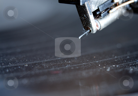 Closeup turntable needle dusty stock photo, a closeup of a turntable needle hovering above dusty vinyl by Jerax
