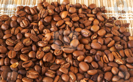 Freshly roasted coffee beans stock photo, Freshly roasted coffee beans on bamboo placemat by Elena Weber (nee Talberg)