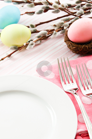Festive Easter Table Setting stock photo, A festive pastel pink table setting is decorated for Easter with traditional dyed eggs and pussy willows leaving ample copy space on a white plate by Karen Sarraga