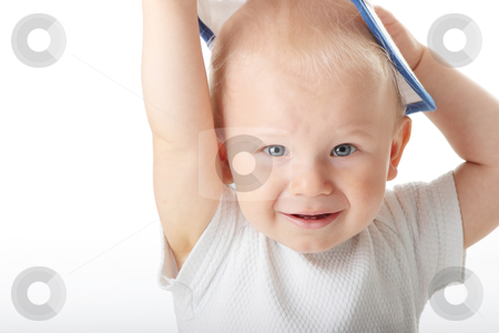 Baby trying on basebal cap stock photo, Adorable baby trying on basebal cap that is way too big for him