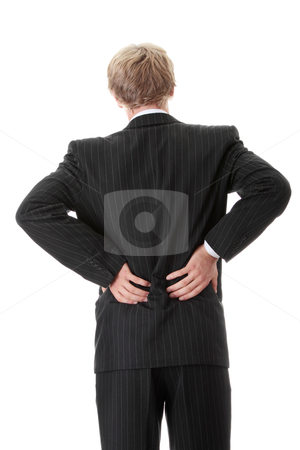 Back ache stock photo, Businessman holding his hand to his aching back  by Piotr_Marcinski