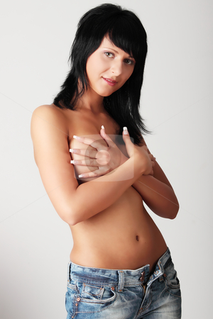 Topless woman with jeans stock photo, Topless woman with jeans covering her breasts with her hands  by Piotr_Marcinski