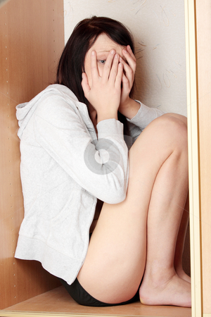 Scared abused woman stock photo, Scared abused woman is hiding her self in closet by Piotr_Marcinski