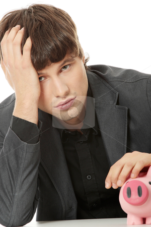Economy crisis concept  stock photo, Young depressed businessman holding piggy bank. Economy crisis concept  by Piotr_Marcinski