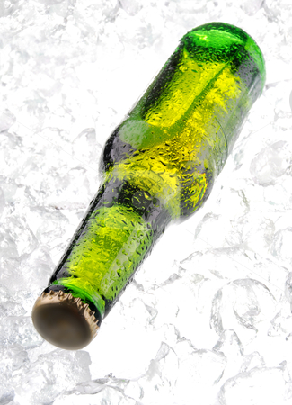 Bottle of beer on ice stock photo, Green bottle of beer on ice  by sutike