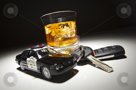 Highway Patrol Police Car Next to Alcoholic Drink and Keys stock photo, Highway Patrol Police Car Next to Alcoholic Drink and Keys Under Spot Light. by Andy Dean