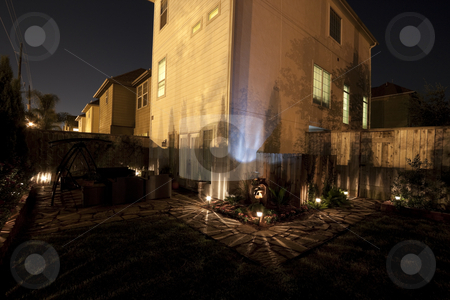 Backyard at Night stock photo, A patio garden or small backyard garden at night with pathway lights by Kevin Tietz