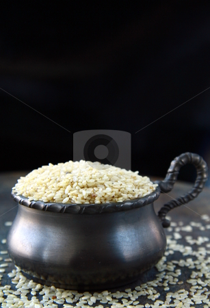 Close up of sesame seeds on a wood table  stock photo, Close up of sesame seeds on a wood table  by Olga Kriger