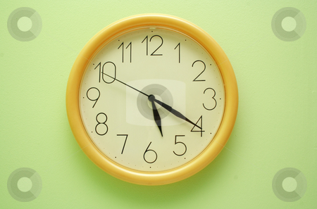 Yellow wall clock on the green stock photo, Yellow wall clock on the green background by vetdoctor