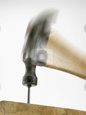 Hammer hitting nail stock photo, A blurred hammer hitting a nail in a piece of timber seen from slightly below, hammer resting on nail head. by russwitherington