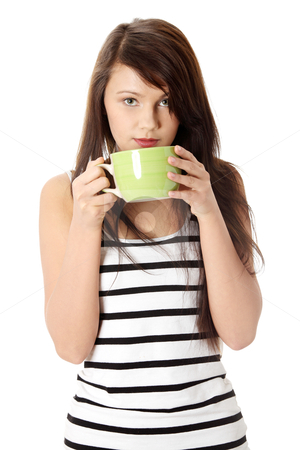 Young woman drinking coffee or tea stock photo, Young woman drinking something hot from big mug by Piotr_Marcinski