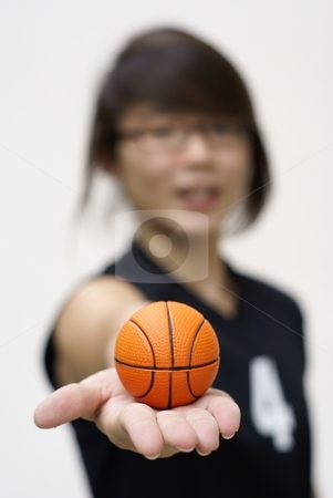 Asian teen holding tiny orange basketball in hand stock photo, ...