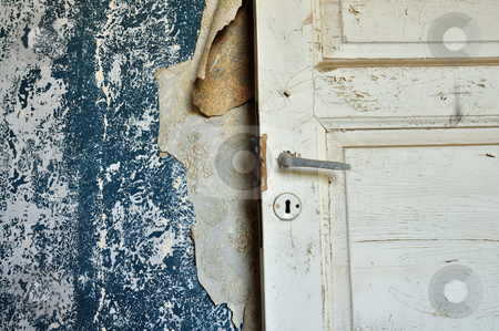 Wallpaper shreads stock photo, Torn vintage wallpaper peeling paint wall and wooden door in abandoned house. by sirylok