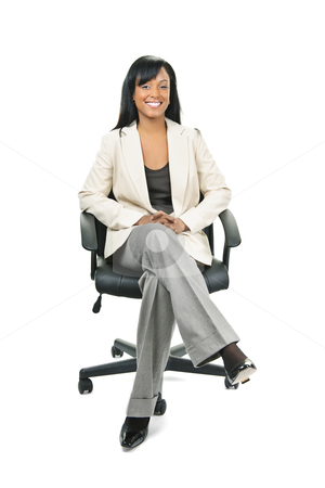 Black businesswoman sitting in office chair stock photo, Young smiling black woman business manager sitting in leather office chair by Elena Elisseeva