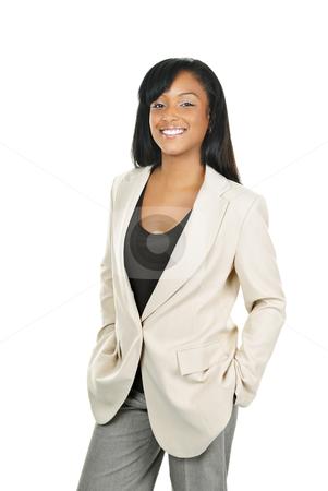 Smiling confident black businesswoman stock photo, Happy young black businesswoman standing isolated on white background by Elena Elisseeva