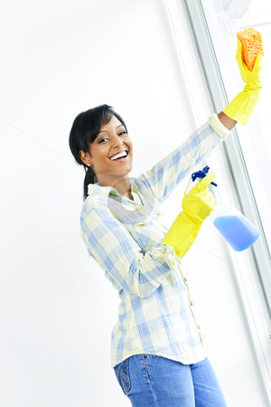 Smiling woman cleaning windows stock photo, Smiling black woman cleaning windows with glass cleaner by Elena Elisseeva
