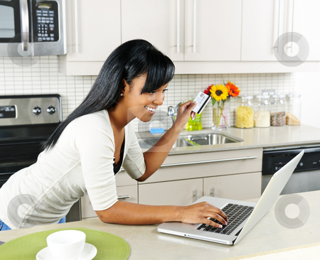 Woman shopping online at home stock photo, Smiling black woman online shopping using computer and credit card in kitchen by Elena Elisseeva