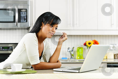 Woman using computer in kitchen stock photo, Thoughtful black woman using computer in modern kitchen interior by Elena Elisseeva