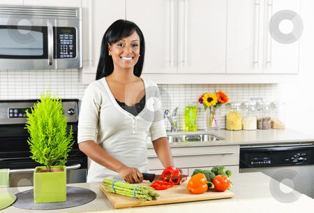 Young woman cutting vegetables in kitchen stock photo, Smiling black woman cutting vegetables in modern kitchen interior by Elena Elisseeva