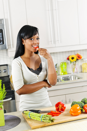 Young woman tasting vegetables in kitchen stock photo, Smiling black woman tasting vegetables in modern kitchen interior by Elena Elisseeva