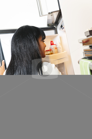 Young woman looking in refrigerator stock photo, Black woman looking in fridge of modern kitchen interior by Elena Elisseeva